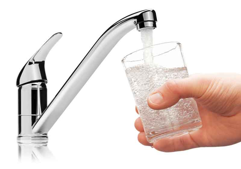 Water faucet filling glass